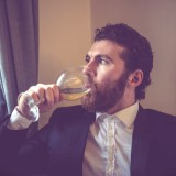 handsome bearded hipster elegant man with glass of wine